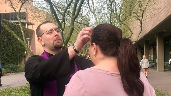 "Rev. Robert Berra of Trinity Episcopal Cathedral applies ""Ashes to Go"" to the forehead of Victoria Bray on Ash Wednesday, February 14, 2018, in Phoenix."