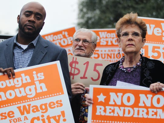 D.A. Robin/Democrat State Rep. Alan Williams, Wakulla County Commissioner Howard Kessler and organizer Barbara DeVane hold signs at a Tuesday rally urging lawmakers to raise the minimum wage. State Rep. Alan Williams, Wakulla County Commissioner Howard Kessler and organizer Barbara DeVane hold signs at a Tuesday rally urging lawmakers to raise the minimum wage to $15 an hour.