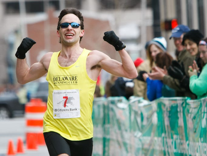 Radley Reist of Bear celebrates as he crosses the finish line.  Runners approach the final hill and cross the finish line on North Market Street at Rodney Square.  Thousands of runners gather for the 51st Caesar Rodney Half Marathon kicking off around Rodney Square in Wilmington Sunday, March 23, 2014.