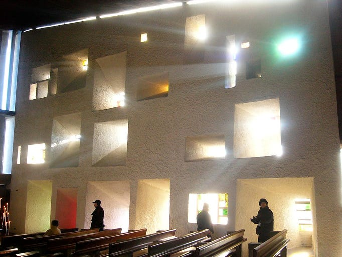 Within the church, sunlight streams through                                                          multi-sized                                                          windows