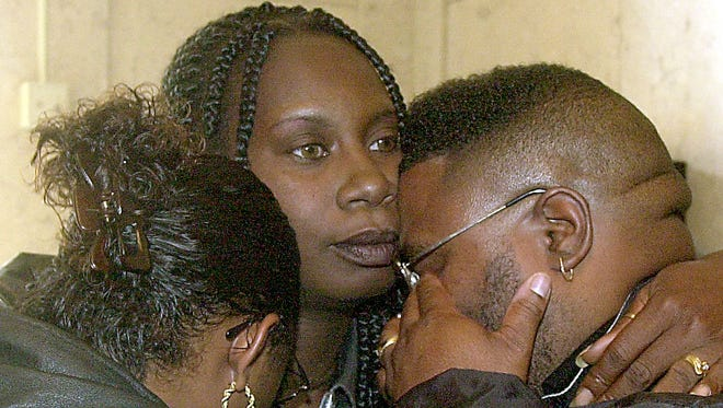September 26, 2001: Timothy Thomas' mother Angela Leisure (center) comforts her sister-in-law Tunja Leisure and her husband Eric Leisure in the Hamilton County Courthouse following the not-guilty verdicts against officer SteveRoach.