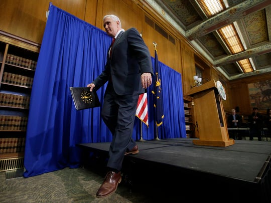 Then-Indiana Gov. Mike Pence steps off the podium after