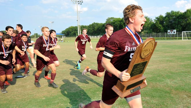 Franklin's Brad Ross carries the trophy in celebration after defeating Collierville 1-0 in the Class AAA Soccer Championship game in Murfreesboro, Tenn., Friday, May 23, 2014.