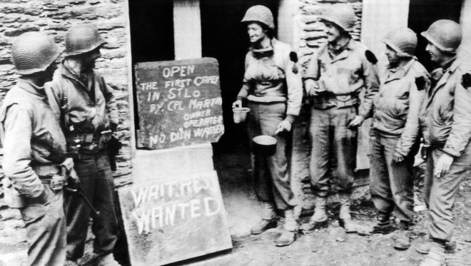 Demonstrating American business initiative, Corp. E.L. Martin (fourth from right), of Martinsville, Va., stands with canteen cup and pan beside a sign announcing the opening of his caf? in the French town of St. Lo, France on July 21, 1944. Prospective customers, the corporalÕs buddies, contemplate the idea of patronizing the first American shop to be established in the town.
