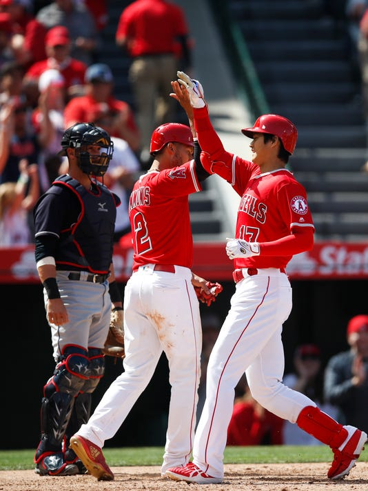 Los Angeles Angels' Shohei Ohtani, right, of Japan, celebrates his two-run home run with Andrelton Simmons as Cleveland Indians catcher Yan Gomes watches during the fifth inning of a baseball game, Wednesday, April 4, 2018, in Anaheim, Calif. (AP Photo/Jae C. Hong)