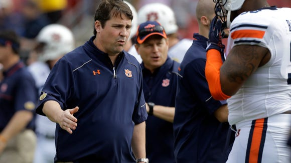 Newly-hired Auburn defensive coordinator Will Muschamp shakes hands with defensive lineman Angelo Blackson before the Outback Bowl on Thursday. Muschamp was the former head coach at Florida.