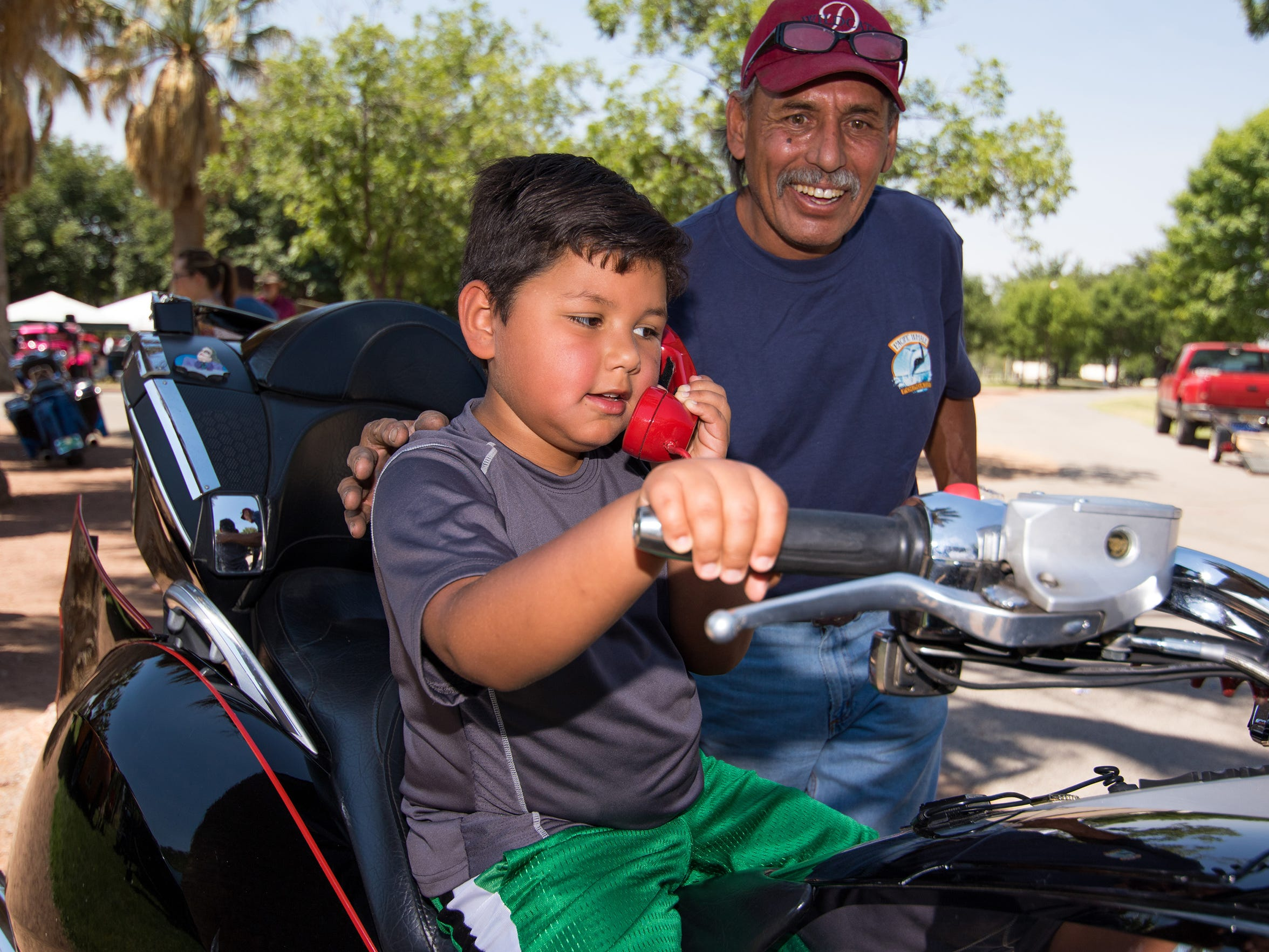 Isidro Calderon reacts as his son Benicio, 8 years old, takes a call on the bat phone while sitting on the Batmobile motorcycle at last year's Kiwanis Kars for Kids Car Show.