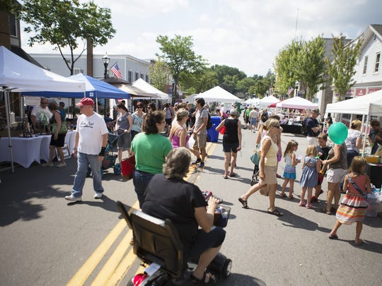 Festivalgoers shop at booths along Union St. at Spencerport Canal Days on July 26, 2015.