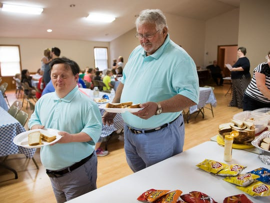 Joel Dill and his father Joe Dill fill their plates