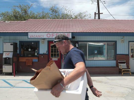 Mike Brown carries belongings through the parking lot