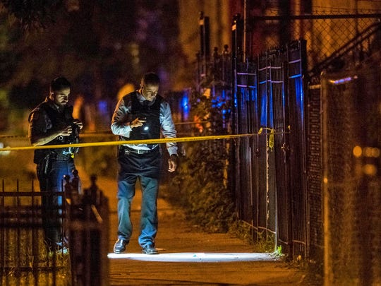 In this Thursday, June 14, 2018 photo, Chicago Police officers investigate the scene where two people were shot in Chicago. A 12-year-old Michigan girl spending the summer in Chicago was fatally shot at the scene, hours after attending a cousin's eighth-grade graduation. Family members at the hospital identified the girl as She'nyah O'Flynn of Covert, Michigan. She and a man who was injured were apparently unintended victims of gunfire from a nearby party. Police say there have been no arrests.