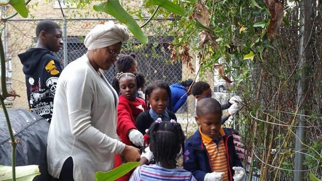 Shakini Aliah, a member at Mosque Masjid Jihad, leads a children's group in collaboration with Mixed Greens to monitor new plants and check soil for growth. Mixed Greens and the mosque have collaborated to help launch a children's garden.