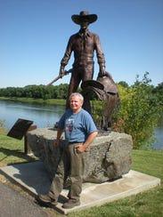 Schildt poses before his bronze statue of Montana actor