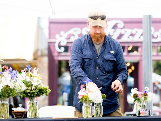 Robin Yeary, of Sevier Blumen, arranges a bouquet of flowers at his booth at the opening day of the 2018 Market Square Farmers' Market in Knoxville on Wednesday.