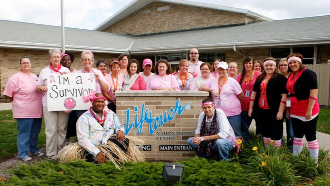 Lifetouch National Contact Center staffers pose for a photo outside of the main entrance of their office in Muncie while wearing pink shirts in honor of breast cancer awareness month on Friday, Oct. 14, 2011.