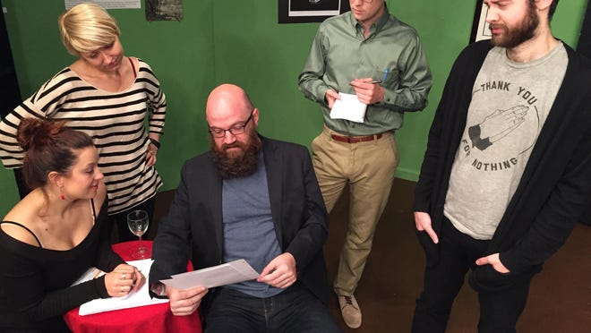 """Leonard (Brian Hinds, center) reviews Izzy's (Beth Tantanella, lower left) newest short story as students played by April Singer, Ryan Watson and Jon Becraft look on in """"Seminar"""" at The Bard's Town."""