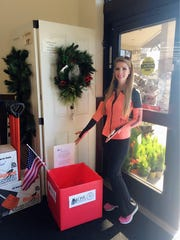 White Sands Chapter of the Daughters of the American Revolution member Mary Louise Rustler shows off a donation box for families in need.