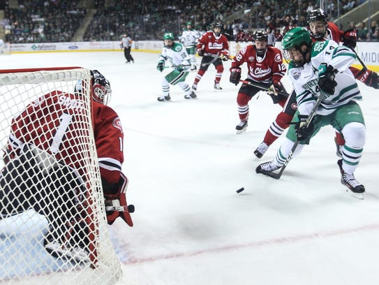 North Dakota's Austin Poganski (right) takes a shot against St. Cloud Statte's Jeff Smith on Feb. 3 at Ralph Engelstad Arena. Poganski, a senior forward and Cathedral High School graduate, has 30 goals and 40 assists in 140 career games with the Fighting Hawks.