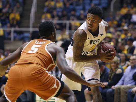 West Virginia guard Daxter Miles Jr. (4) looks to make a pass while being guarded by Texas guard Kendal Yancy (5) during the second half of an NCAA college basketball game, Monday, Feb. 20, 2017, in Morgantown, W.Va. West Virginia defeated Texas 77-62. (AP Photo/Raymond Thompson)