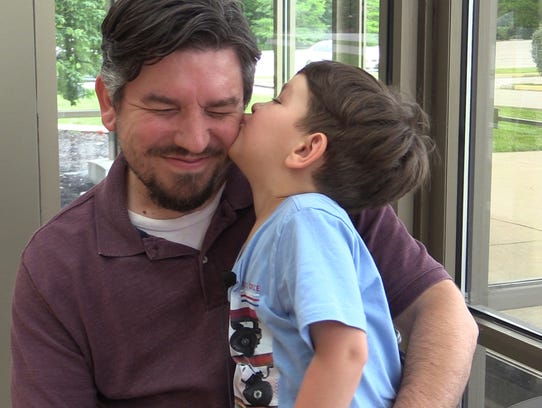 Chrisitiano Tripure, 3, kisses his dad Greg Tripure.