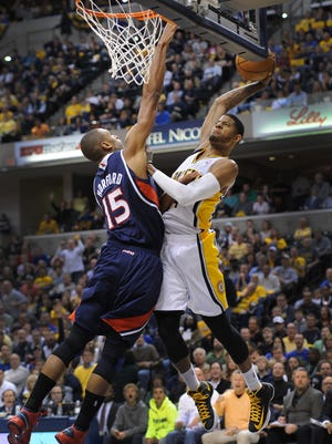 Indiana Pacers Paul George,right, goes up for a dunk on Atlanta Hawks Al Horford,left, in the first game of their NBA Playoffs  Sunday afternoon at Bankers Life Fieldhouse.