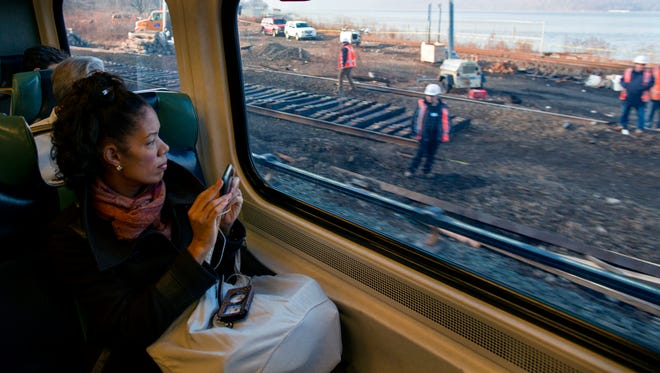 Passengers on a Metro-North train view ongoing repair work near the Bronx station where a train derailed Sunday.