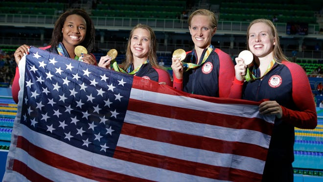 From right to left, United States' Lilly King, Dana Vollmer, Kathleen Baker and Simone Manuel display their gold medals for the women's 4 x 100-meter medley relay final during the swimming competitions Saturday at the 2016 Summer Olympics.