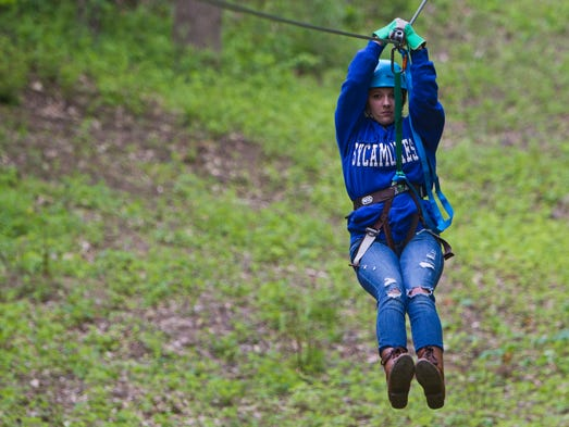 Brooke Cummings of Crawfordsville comes down one of the lines at Indiana Zipline Tours for her birthday present by her boyfriend Jacob Bonebrake Saturday, May 17, 2014, near Crawfordsville. The zip line company held their grand opening Saturday featuring 8 lines that take visitors across green meadows and flowing streams in a wooded 60-acre lot.