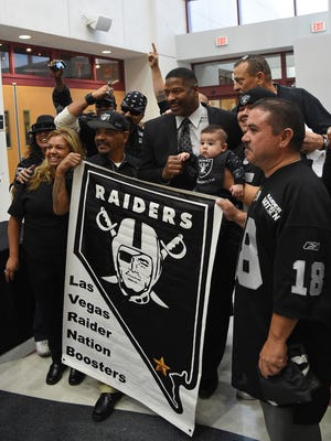 Former Oakland Raiders player Napoleon McCallum, center, poses with Raiders fans as he arrives at a Southern Nevada Tourism Infrastructure Committee in Las Vegas in 2016.