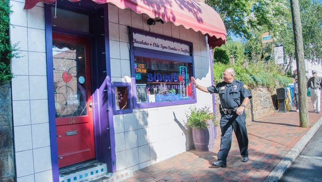 Black Mountain police officer Buster Gray walks by Sweet on Cherry Street, part of the downtown beat  he's had for three years.