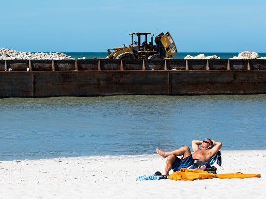 A construction barge sits stranded at Lowdermilk Park in Naples on Wednesday, Jan. 31, 2018. The barge, along with another that has since been removed, is suspected to have drifted from Doctors Pass with the tide two nights ago.