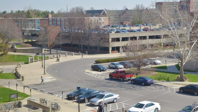 Cars are visible parked along the drive and in the parking garage near Emens Auditorium on the Ball State University campus.