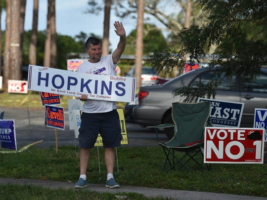 John Mario, of Port St. Lucie, campains for his friend Bobby Hopkins at Parks Edge recreation center on Langdale Boulevard on Tuesday, Nov. 8, 2016 in Port St. Lucie.