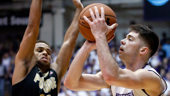 Northwestern guard Bryant McIntosh, right, shoots against