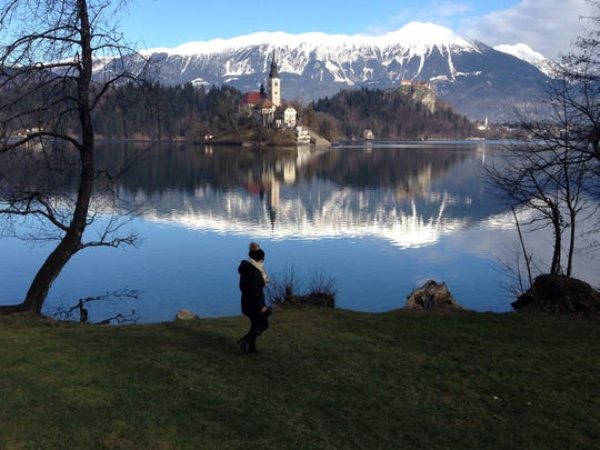 A woman walks by the Lake Bled in Slovenia with a island and the Church of Our Lady on it. Tucked in the northwestern corner of Slovenia, between Austria and Italy, stands a spectacular landscape: a lush tiny island in the middle of the emerald-green lake waters, with a church tower peeking out of the evergreens, surrounded by snow-covered rocky Alps.