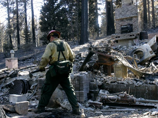 Steve Meadows of the U.S. Forest Service does mop up work at a home that was burned down on Sunday in the Angora wildfire near South Lake Tahoe, Calif., on Thursday, June 28, 2007. (AP Photo/Jeff Chiu)