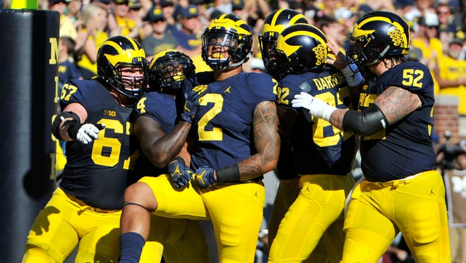 Teammates celebrate with Michigan tight end Devin Asiasi (2) after his touchdown in the second quarter.