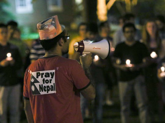 """Nepali student Swapnil Baral wears a """"Pray for Nepal"""" sign on his shirt while reciting a poem about his feelings immediately after the Nepal earthquake during a candlelight vigil at the University of Delaware on Tuesday."""