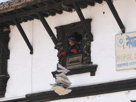 A police officer throws papers out of the window of a post office in Kathmandu, Nepal that has been condemned due to earthquake damage following a 7.8-magnitude earthquake.
