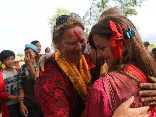 Dagsboro, Del. residents Amy and Holly Kaufman hug after being welcomed by villagers of the Katunge village development community. The mother and daughter donated tin for 162 families to help them build semi-permanent structures to withstand the monsoon season.