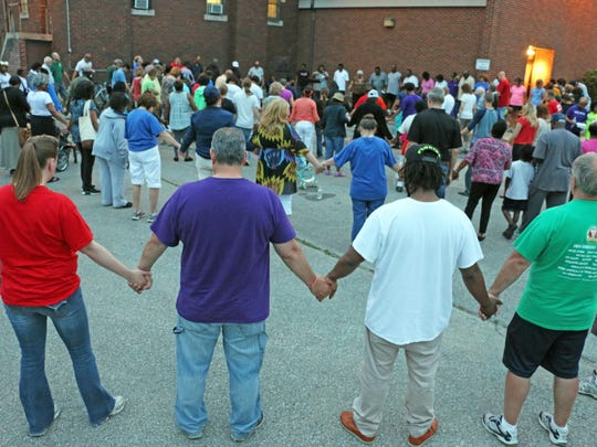 """Marchers hold hands to pray near the end of a """"Jericho Walk"""" march and rally on Sunday, June 7, in Waterloo."""