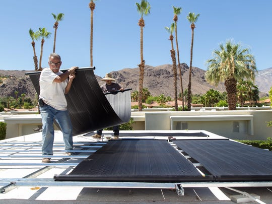 Sun Up Energy workers, Lupe Cruz, right, and Hipolito Herrerra install solar arrays on top of a home in the Coco Cabana Homeowner's Association in Palm Springs. Zoe Meyers/The Desert Sun Sun Up Energy workers, Lupe Cruz, right, and Hipolito Herrerra, install solar arrays on top of a home in the Coco Cabana Homeowner's Association in Palm Springs, Calif., Tuesday, June 17, 2014.