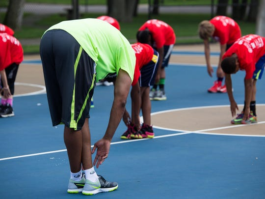 Former Portland Trailblazer Desmond Ferguson leads a group of young people in warmup exercises for the Spirit of Reaching Higher Levels Basketball Clinic at Claude Evans Park on Friday afternoon.