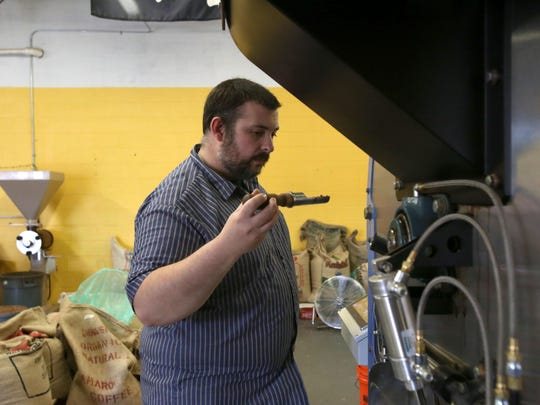 Ithaca Coffee Company's head roaster, Chris Ganger, smells and checks the coffee at different stages of the roast.