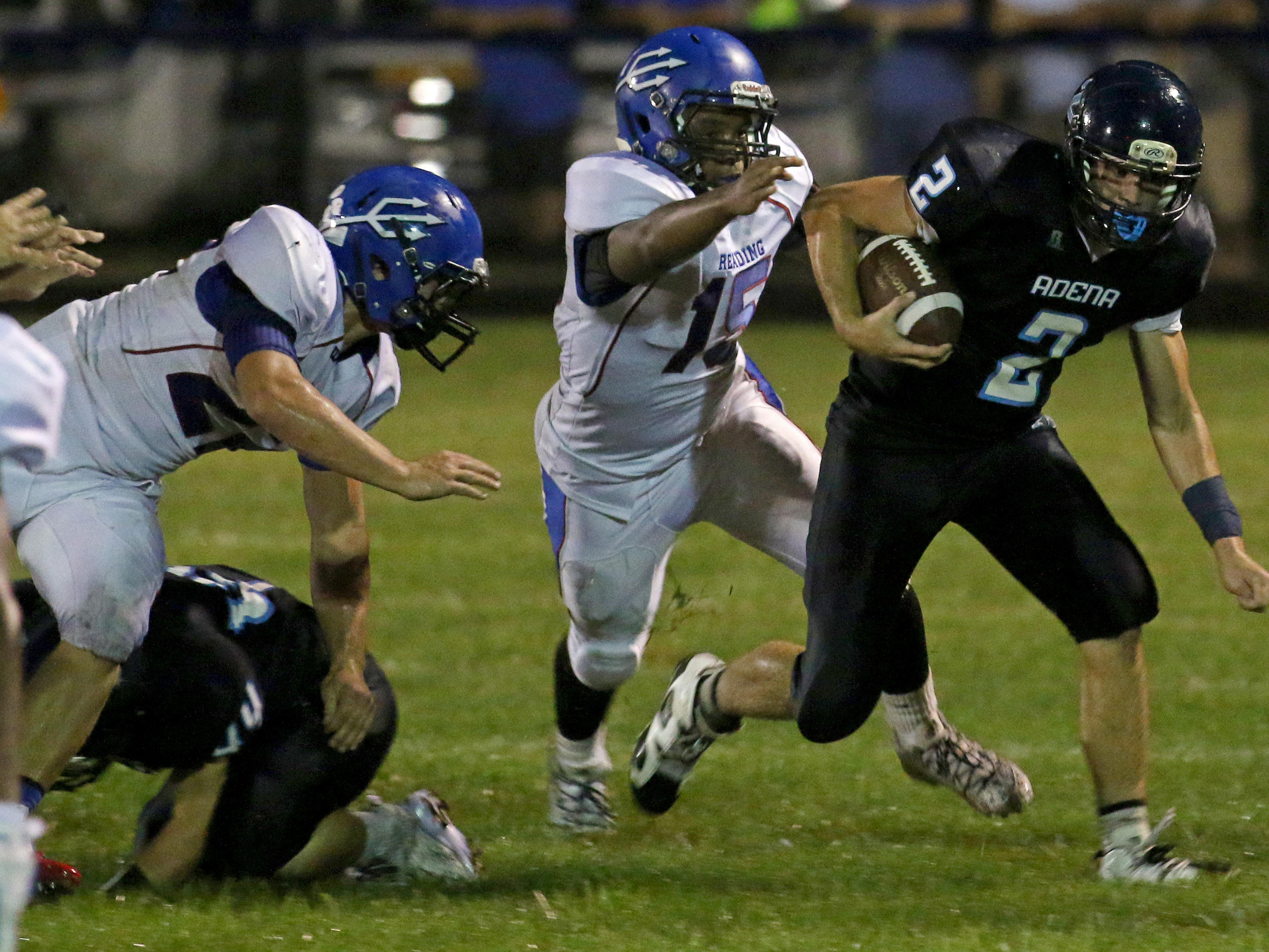 Adena's Cale Free breaks through a tackle against Cincinnati Reading, Friday night. Reading beat the Warriors, 41-12.