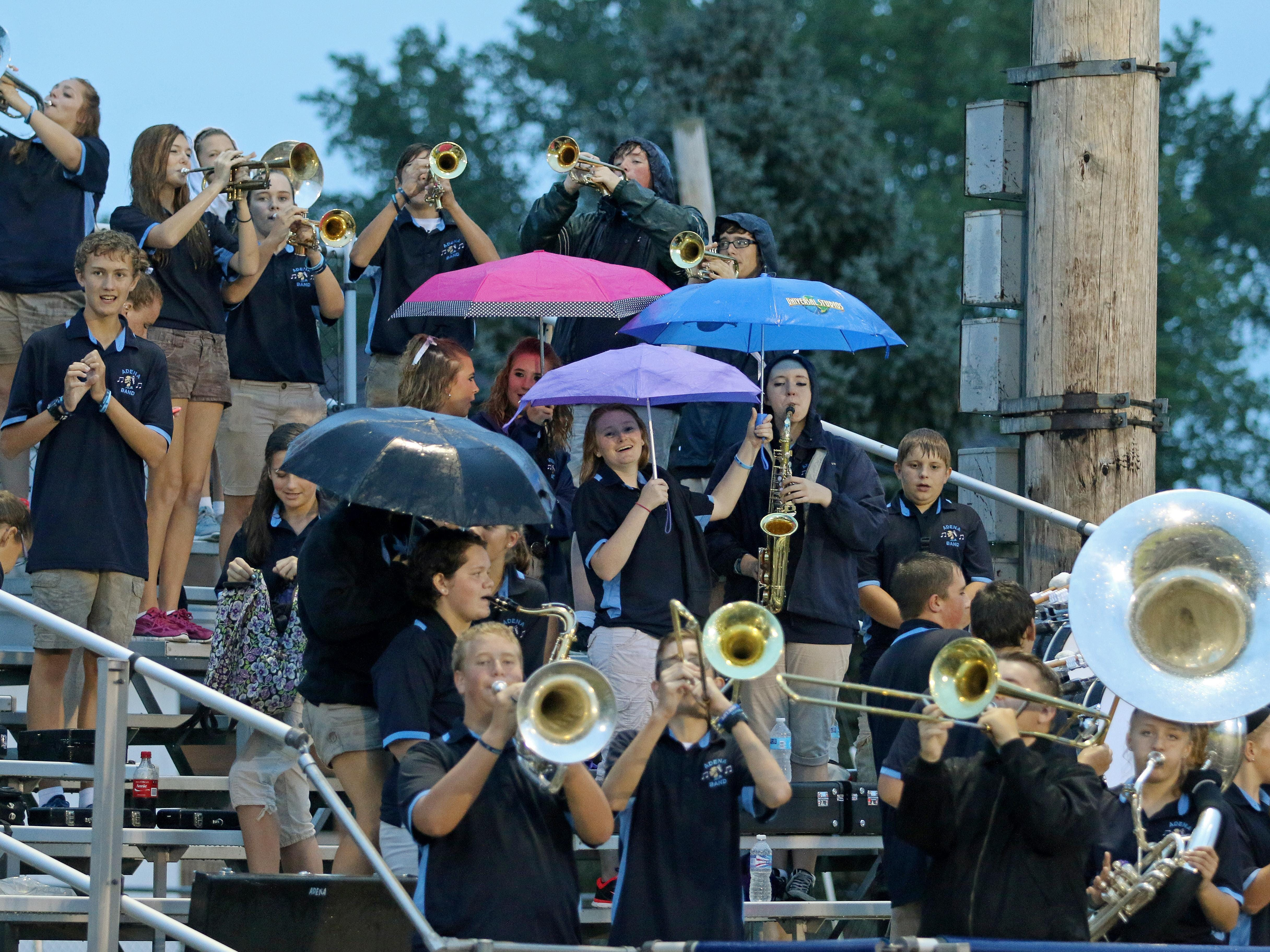 Members of the Adena High School marching band seek shelter from the rain underneath umbrellas during Friday's game. Despite being delayed, Adena played against Cincinnati Reading at Adena. The final score was Cincinnati Reading, 41, Adena 12.
