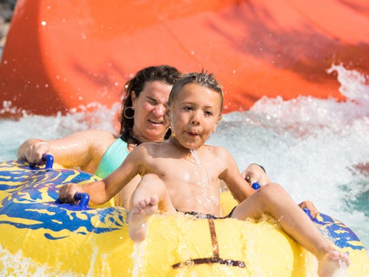 Jacki Carpenter and her nephew Larson Cardella tube down the waterslide at Flash Flood Water Park's Community Appreciation Day on Monday afternoon.