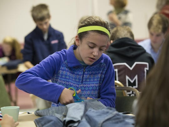 """Katie Antmann, 13, of Madison, cuts pattern pieces out of a pair of donated blue jeans. The United Methodist Church in Madison held a """"Sole Cutting Party"""" where some 40 members of the church and community cut pattern pieces out of donated blue jeans to make shoes for children in Uganda."""