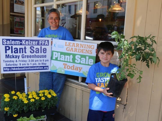 Grant Elementary School first grader Alessandro Perez and SKEF Gardens' Brenda Knobloch have healthy plants for sale.