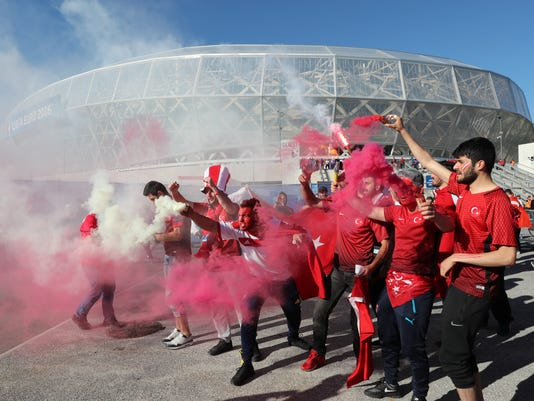 Turkish soccer team supporters hold flares and fire crackers as they cheer ahead of the Euro 2016 Group D soccer match between Spain and Turkey at the Allianz Riviera stadium in Nice, France, Friday, June 17, 2016. (AP Photo/ Claude Paris)